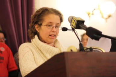 Nicole LeBlanc speaking into a podium microphone