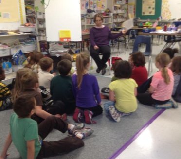 Nicole LeBlanc reading a book in an elementary school classroom to a group of students