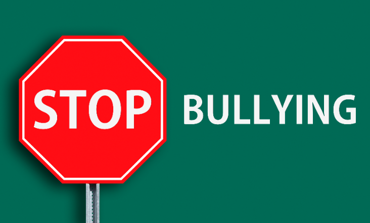 """Red stop sign with the word """"stop"""" next to the word """"bullying"""". There is a green background."""
