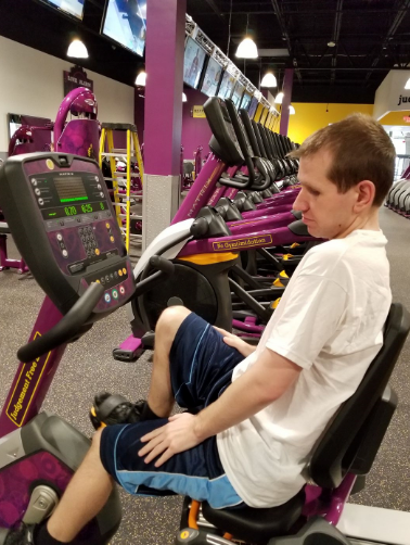 Kyle sitting on a stationary bike at a gym.
