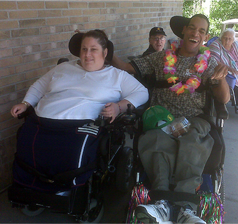 A woman and man sitting next to each other in wheelchairs. The man has his arm around the woman and he is smiling.
