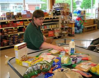 Picture of Abby bagging groceries at the grocery store.