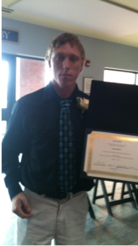 Man in dress clothes standing and holding a certificate.