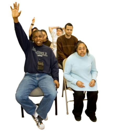 A group of self-advocates sitting in three rows of chairs. Two people have their hand raised.