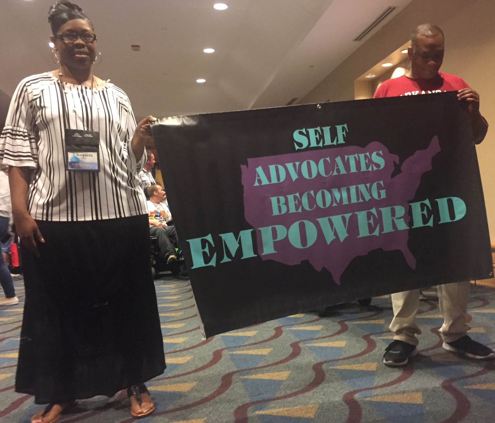 Two People Holding A Banner That Says Self Advocates Becoming Empowered