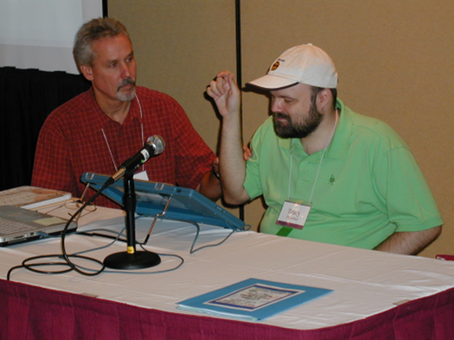 Picture of Tracy presenting with another man. They are sitting behind a table and there is a microphone on the table.