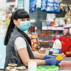 A cashier wearing gloves and a mask