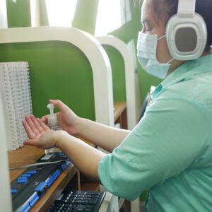 Disability blind person with headphone wearing face mask applying alcohol gel hand sanitizer on hands before using computer with braille display amid Coronavirus (COVID-19) pandemic.