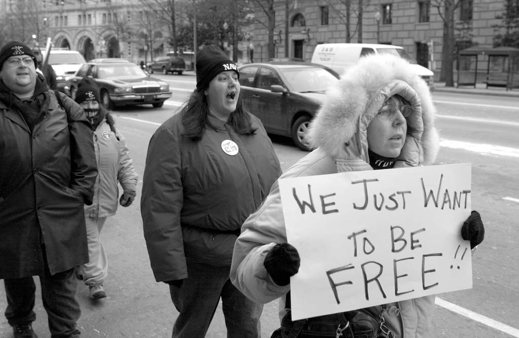 """People dressed in winter clothing walking next to a busy street. The person in front holds a sign that reads """"We just want to be free!"""""""
