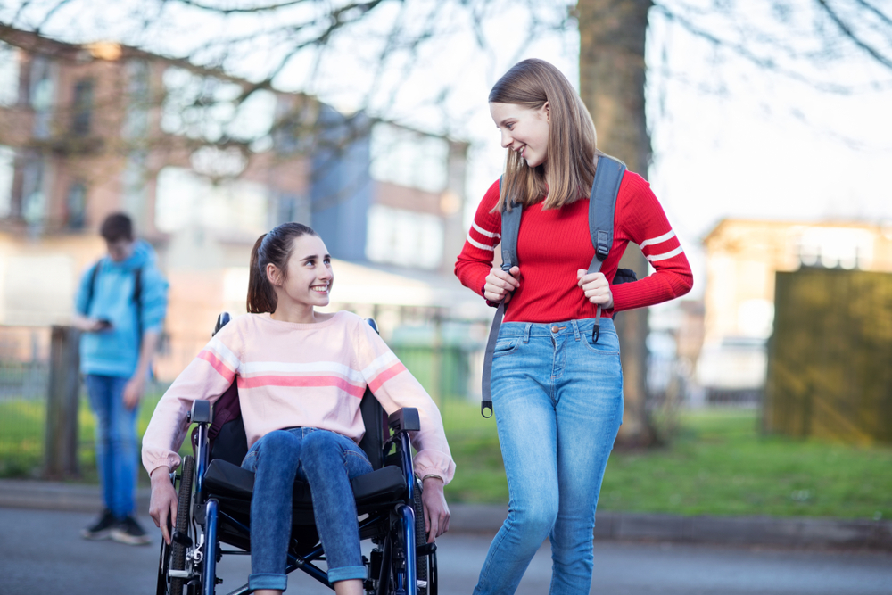 Two girls looking at each other and smiling. One is in a wheelchair. The other is standing and wearing a backpack.