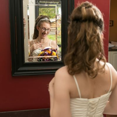 A woman in a wedding dress touching her necklace and looking down, smiling. The photo is from behind but the woman's face is visible in a mirror.