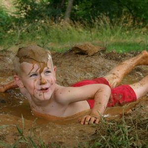 A boy lying on his stomach in the mud. He is looking up to the side and smiling.