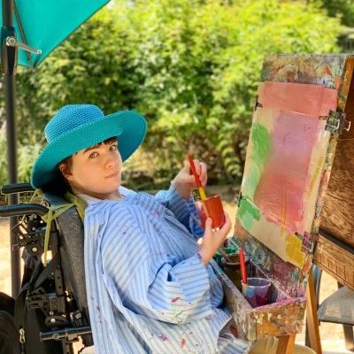 A person sitting in a wheelchair in front of an easel, painting. They are looking to the side at the camera.